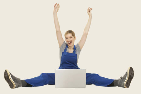 workwoman: Woman in overall sitting with laptop and cheering