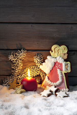 Gingerbread christmas angel against wooden background photo