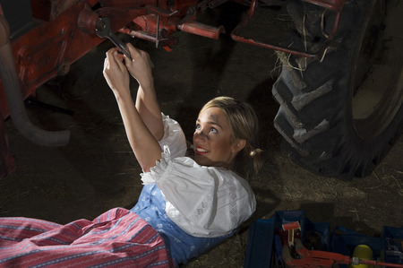reversal: Young woman repairing tractor, portrait