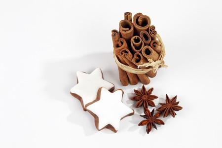 Bundle of cinnamon sticks staranises christmas pastries on white background