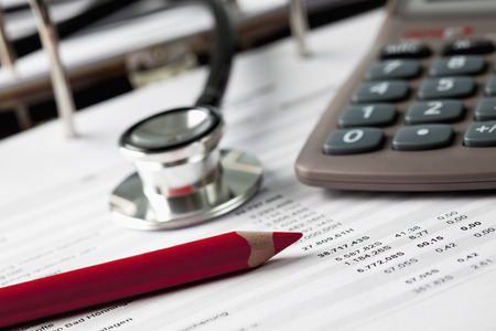 Calculator with pen and stethoscope and form, close up Stock Photo