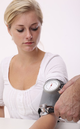 Doctor is measuring a young blonde woman blood pressure photo