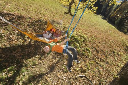 Austria, Salzburger Land, Altenmarkt, Mother watching son playing on swing photo