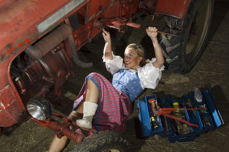 ��role reversal�: Young woman repairing tractor, portrait