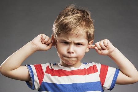 oido: Muchacho que cubre los o�dos j�venes contra el fondo gris Foto de archivo