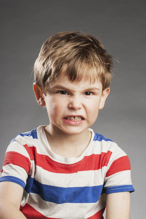 clenching: Young boy looking sad at camera against gray background