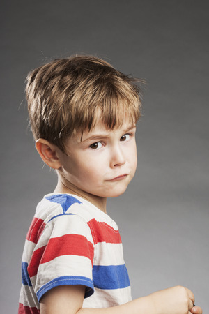 Young boy looking sad against gray background, side view photo