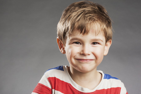 young boy smiling: Happy young boy smiling against gray background Stock Photo