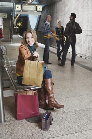 subway platform: Germany, Bavaria, Munich, four Persons on subway platform woman sitting holding bag smiling Stock Photo