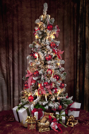 Decorated christmas tree with electric candles and presents photo