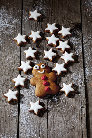 gingerbreadman: Cinnnamon stars with gingerbreadman on wooden background