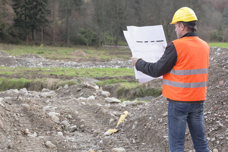 site map: Architect is standing in a construction site looking in a construction plan