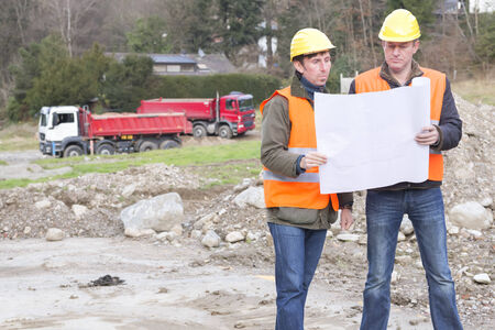 projekt: Projekt manager and architect standing in construction site looking at blueprint