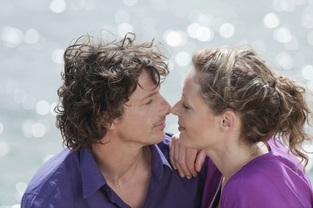 rubbing noses: Spain Mallorca Couple rubbing nose together ocean in background Stock Photo