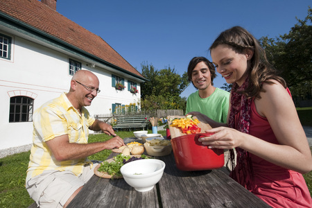Germany, Bavaria, Two men and woman at table in garden preparing food photo