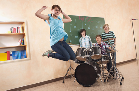 Students at music class girl jumping smiling  boy playing drums classmates standing behind photo
