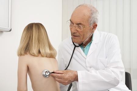 Doctor examining girl with stethoscope Stock Photo