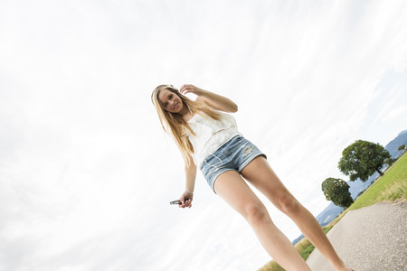 Young woman listneing to music walking on road low angle view 版權商用圖片