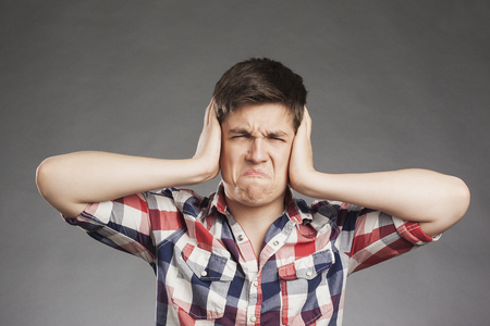 ear checked: Portrait of teenager boy covering ears Stock Photo