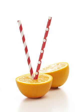 drinking straw: Arance fresche e mezzo con cannuccia su sfondo bianco