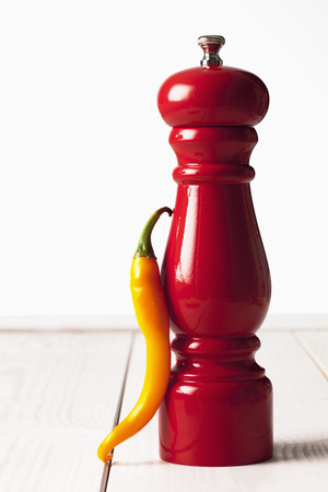 pepper grinder: Yellow chili and red pepper grinder on white wooden table