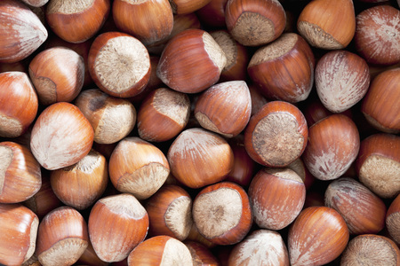 unpeeled: Unpeeled hazelnuts as background, close up