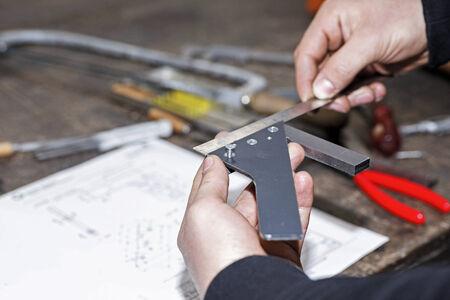 metalworker: Trainee in workshop working on piece of metal Stock Photo