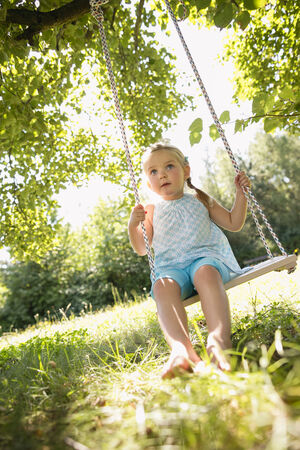 Young girl sitting in swing in garden photo