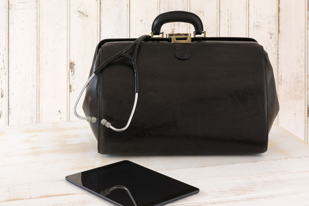 Home call, doctors bag with stethoscope and Tablet photo