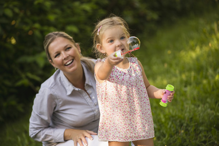 Mother and daughter blowing soap bubbles in garden photo