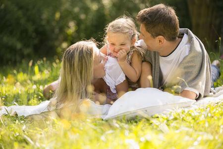 Young family relaxing in garden photo