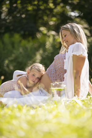 Pregnant mother and daughter in garden daughter listening to mothers belly photo