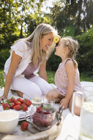Mother and daughter having picnic in garden photo