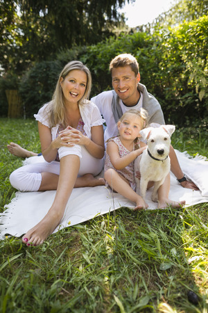 lifting jack: Young family sitting in garden with white jack russel