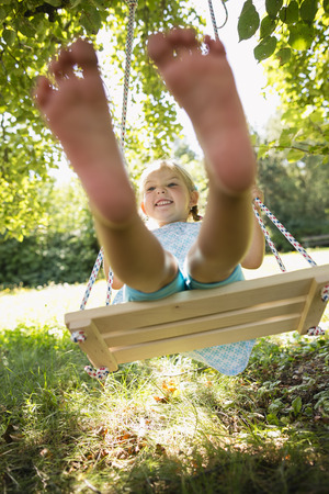 Young girl sitting in swing in garden