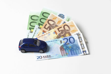 fanned: Toy car and fanned euro notes on white background