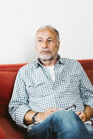 contemplative: Contemplative senior man sitting on sofa