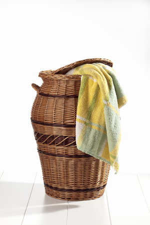 Laundry basket with towel on white background photo
