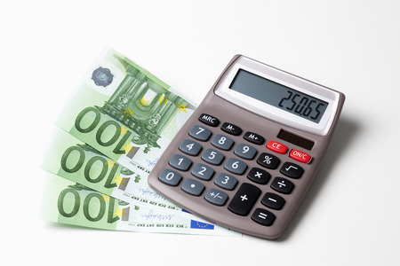 fanned: Calculator with fanned Euro notes and coins on white background