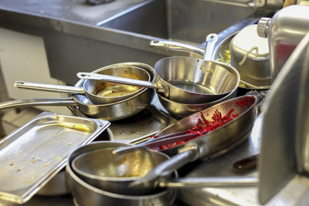 Kitchen in restaurant, sink filled with dirty metal dishes