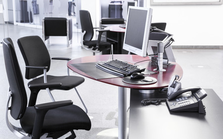 Empty open-plan office with desks chairs computers