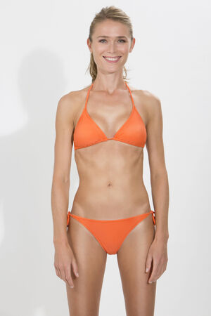 vertical format: Young blonde woman in orange bikini standing against white background