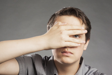 obscuring: Teenager boy against gray background covering eyes, peeking Stock Photo