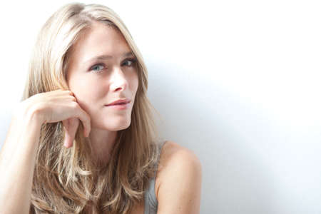 sceptical: Portrait of young blonde woman against white background, hand on chin