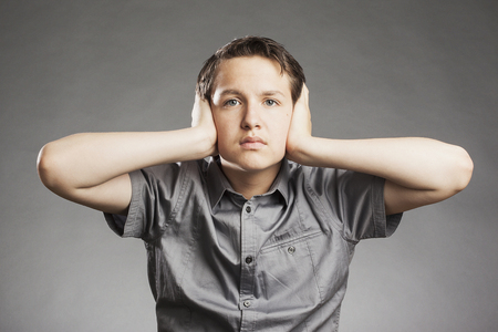 Teenager boy against gray background covering ears with hands photo