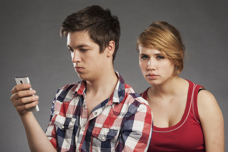 argues: Teenager couple, boy using smartphone, girl wants attenion