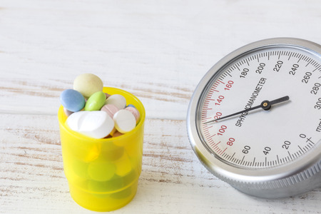 blood pressure gauge: Blood pressure gauge with yellow pill box next to it, close up Stock Photo