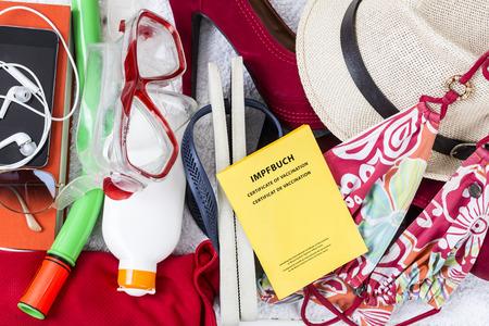 sandalias: Preparación para las vacaciones, el equipaje con el traje de baño, toalla, gafas de sol, crema solar, chanclas, sombrero de paja, pase vacunación
