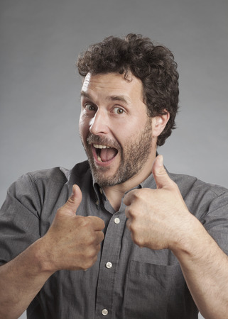 triumphing: Man in grey shirt showing thumbs up