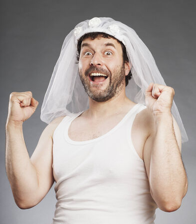 exultant: Middle-aged man with a full beard, in undershirt with bridal veil, exultant Stock Photo